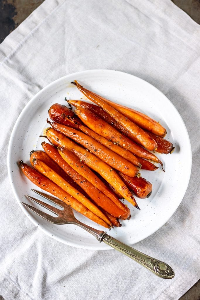 Plate of roasted glazed carrots with a vintage serving fork.