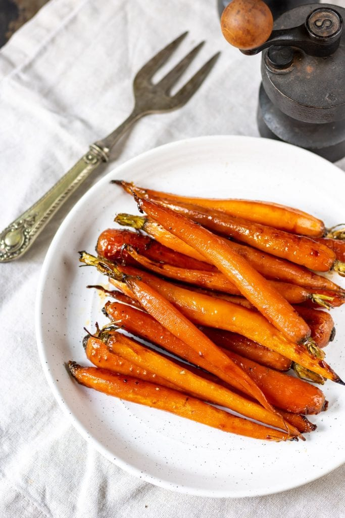 Glazed carrots on a plate, next to a vintage fork.