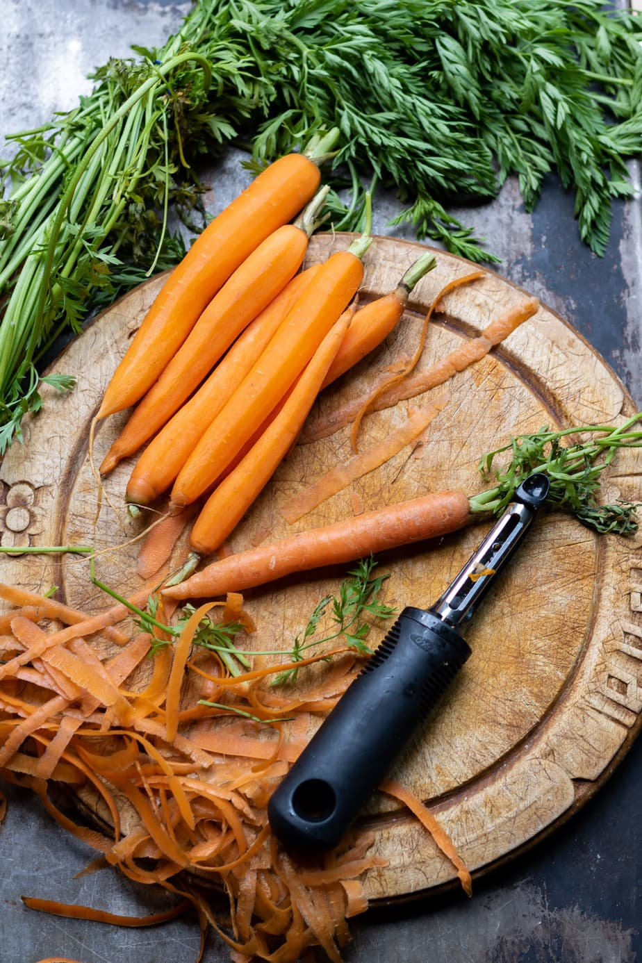 Carrots being peeled on a board.