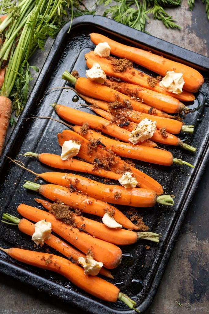 Baking tray with carrots, butter, sugar and maple syrup.