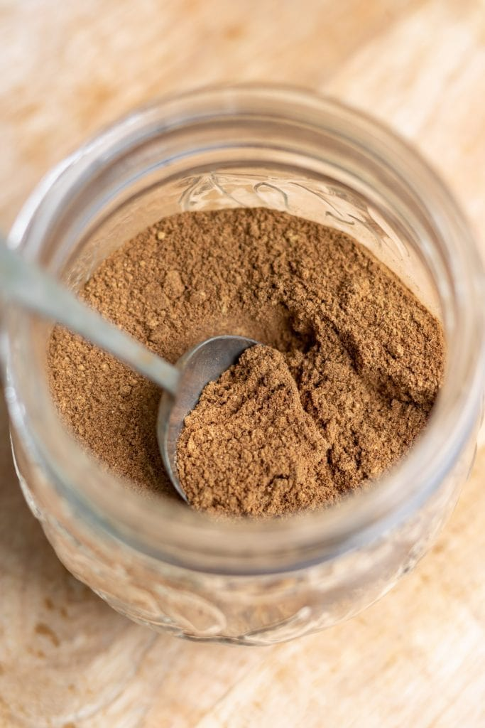 Spoon in a jar of spice mix.