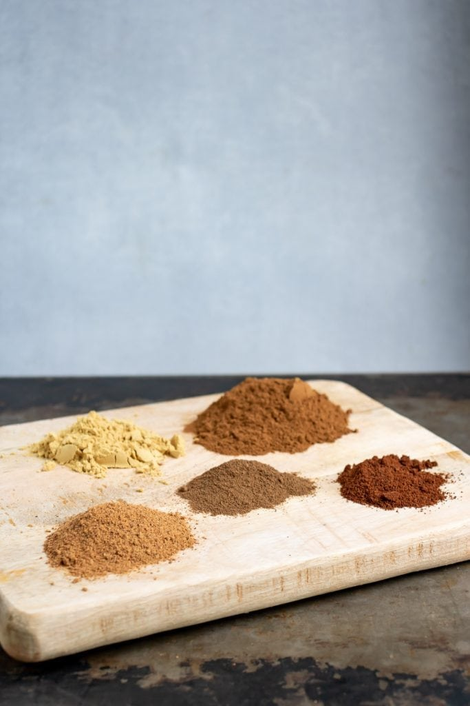 Wooden board with piles of spices.