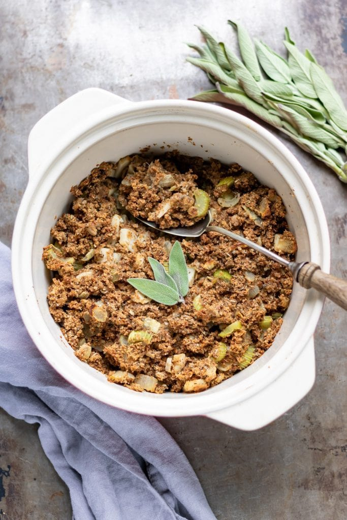 Casserole dish of Vegan Stuffing with sage leaves on top.