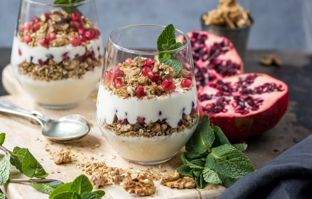 Two granola parfaits on a board, with pomegranates.