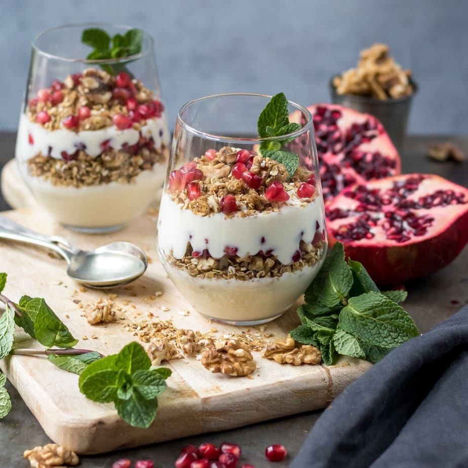 Two yogurt granola parfaits in glasses.