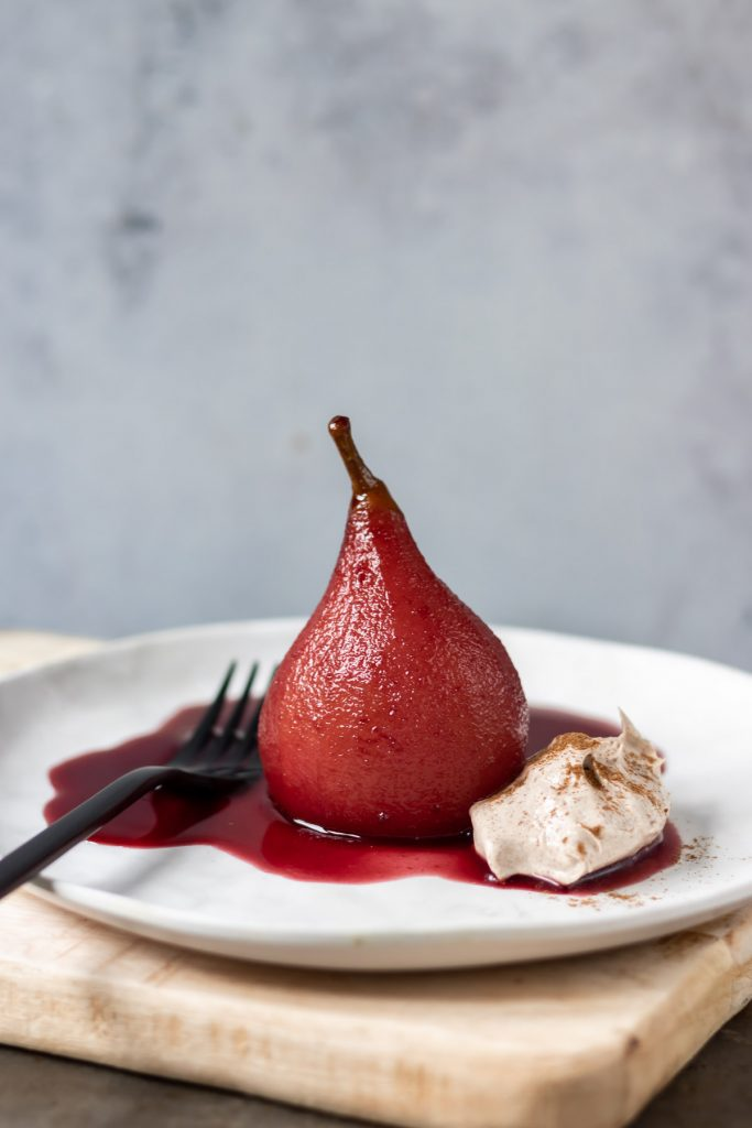 Poached pear on a plate with spiced wine syrup and cream.