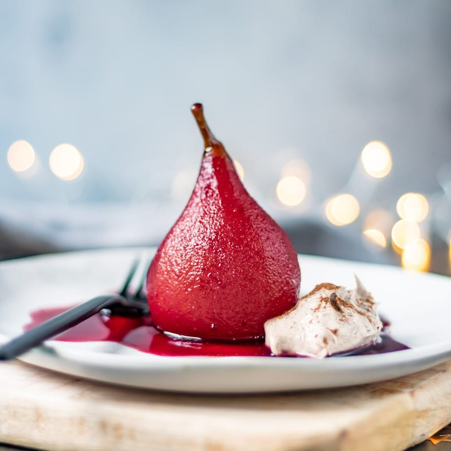 Red wine poached pear on a plate with cinnamon cream.