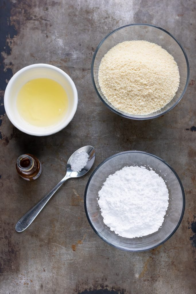 Almond paste ingredients on a table: almond meal, icing sugar, egg whites, almond extract and salt.