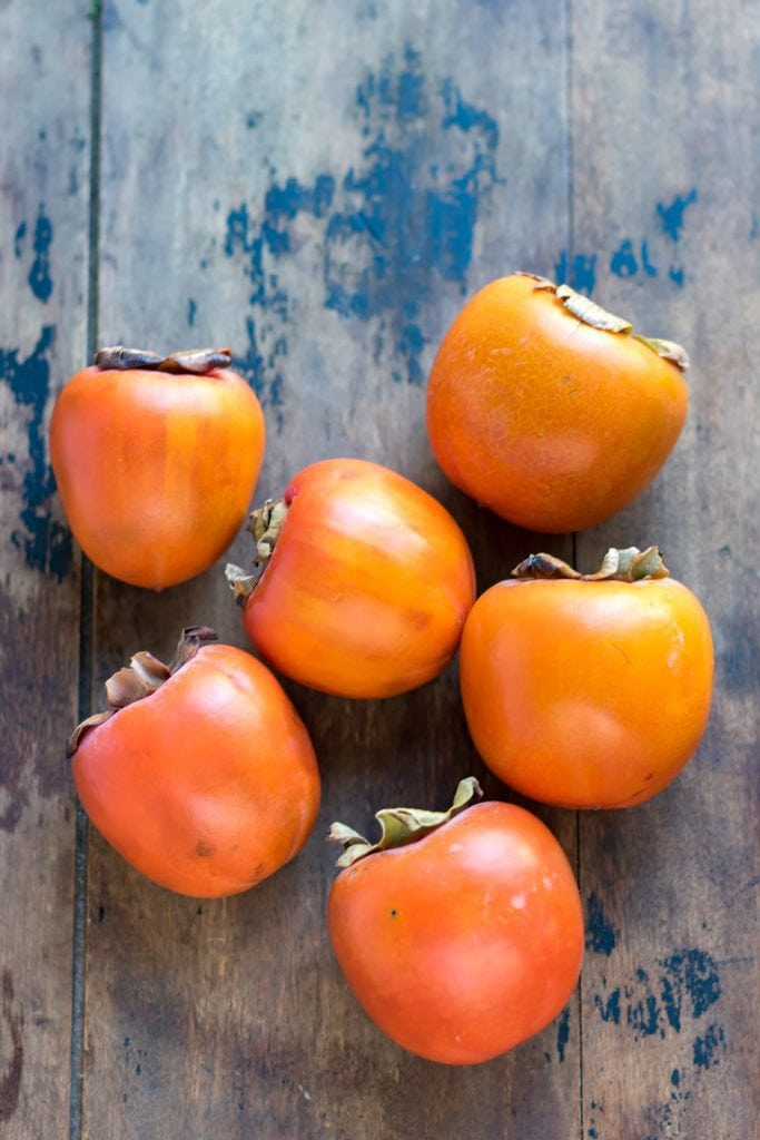 Hachiya persimmons on a wooden table.