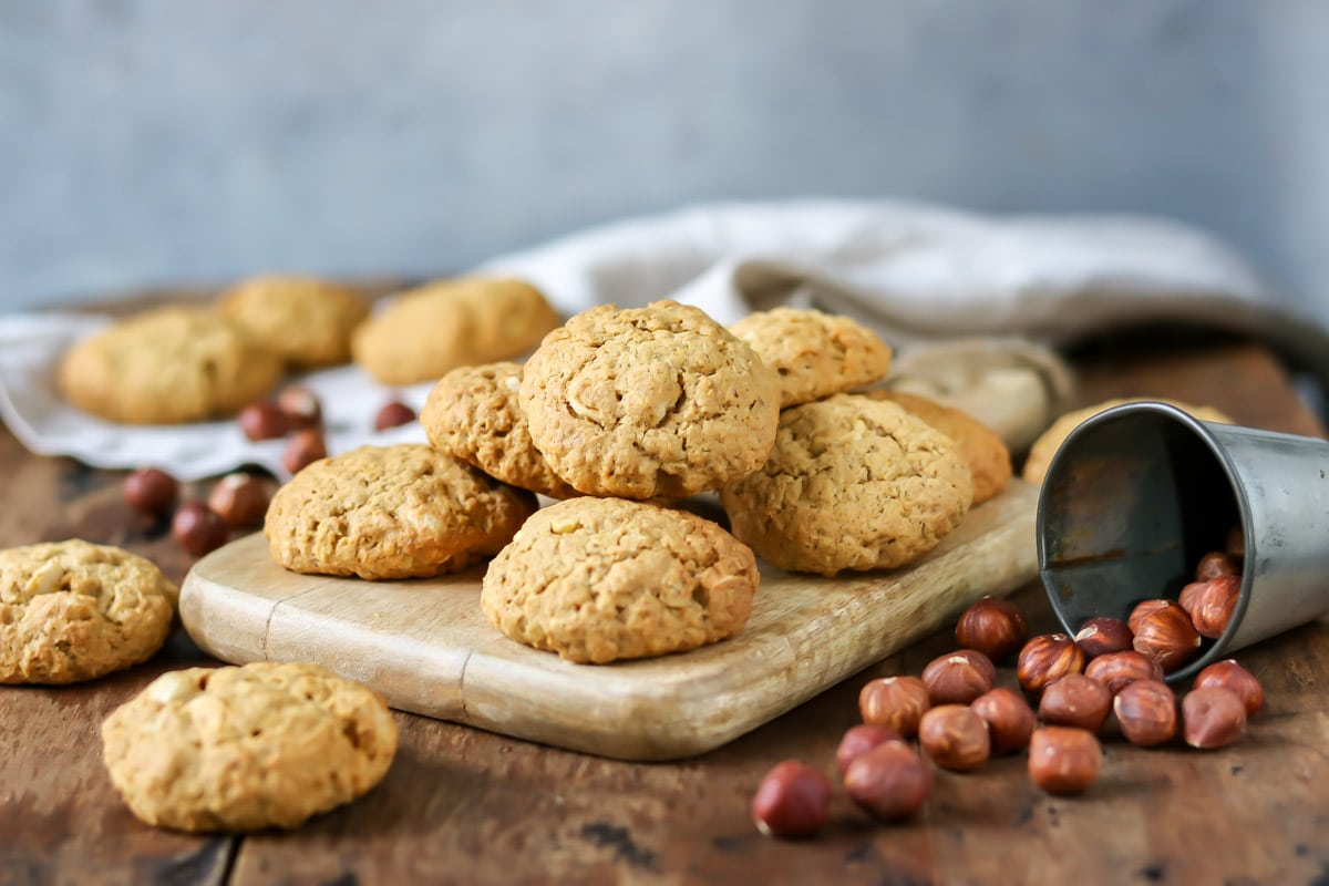 Pile of cookies on a board next to hazelnuts.