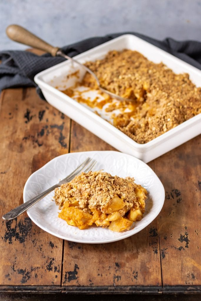 Plate of pumpkin crisp with baking dish in the background.