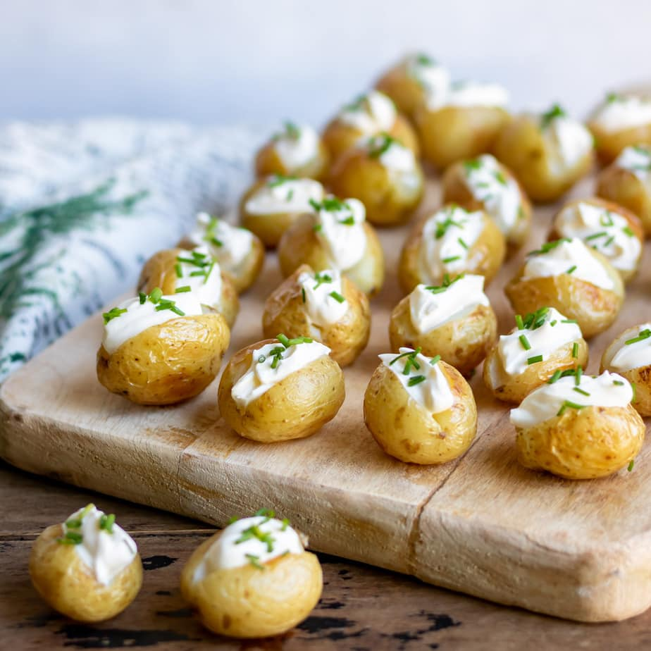 A serving board with mini baked potatoes.
