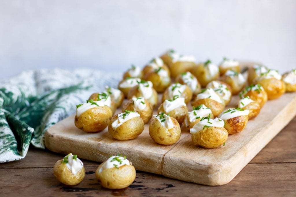 Rows of mini baked potatoes with sour cream on a board.