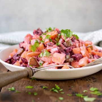 Dish of rosolli salad with a serving spoon.