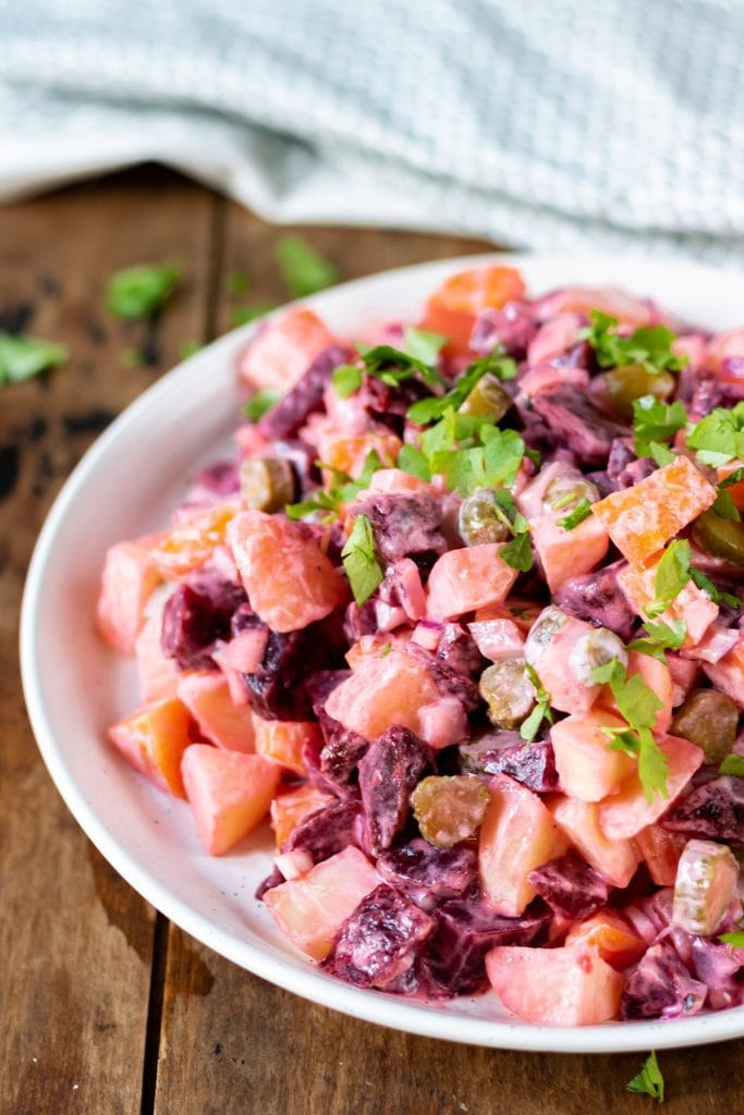 Close up of a dish of beetroot and root vegetable salad.
