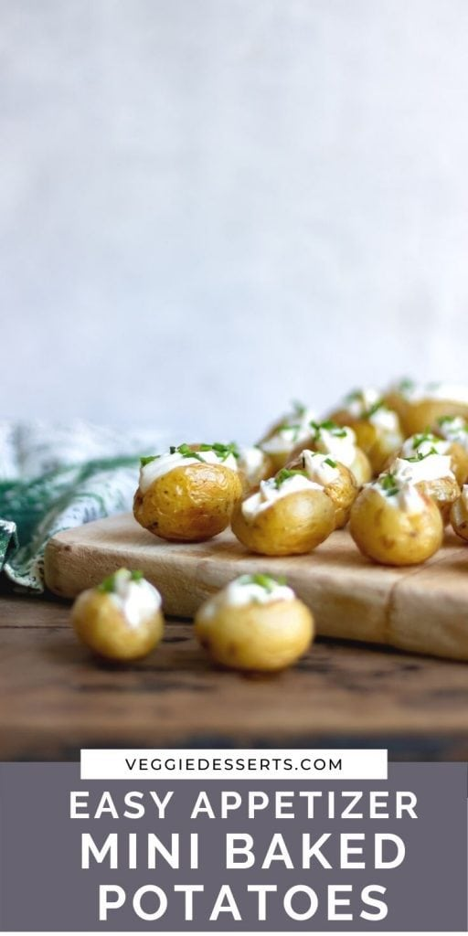 New potatoes on a board with sour cream and chives and text: easy appetizer mini baked potatoes.