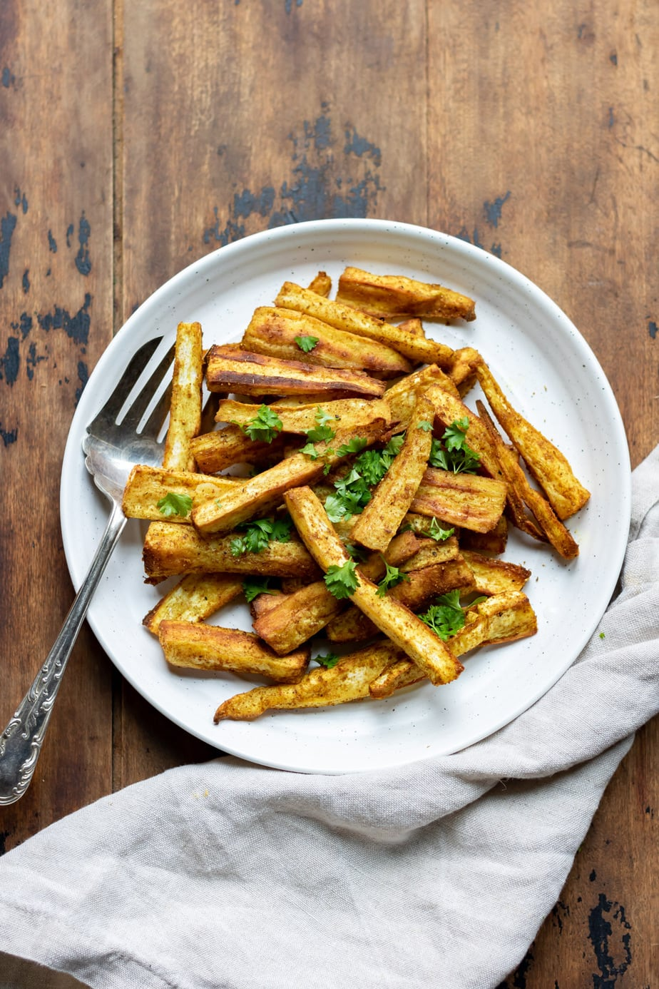 Wooden table with plate of parsnip fries.