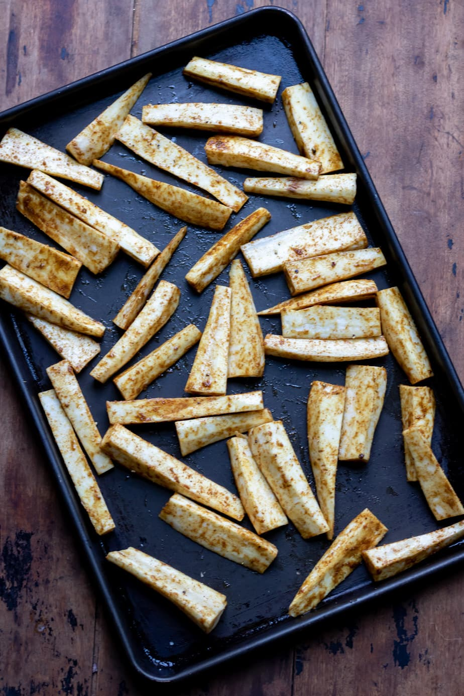 Parsnip sticks covered in spice on a baking tray.