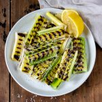 Plate of grilled leeks with a wedge of lemon.