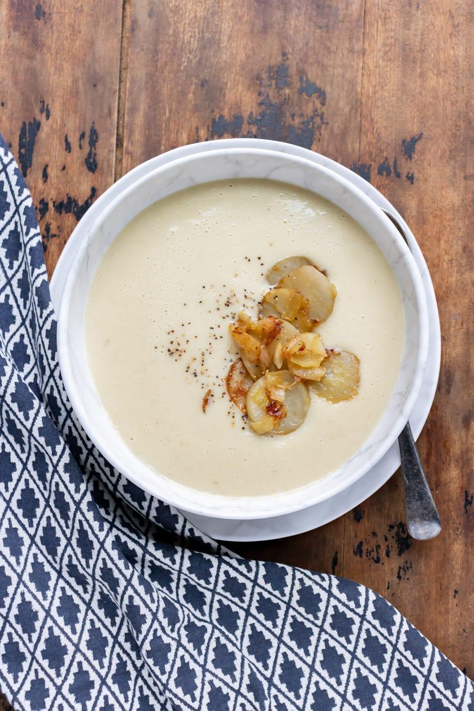 Bowl of jerusalem artichoke soup next to a napkin.