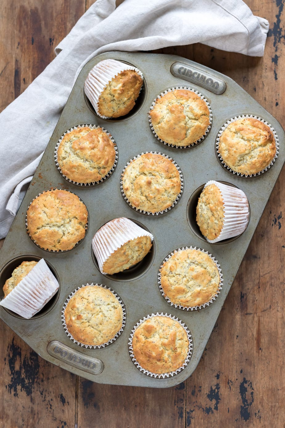 Muffins in a muffin tray with some on their side.