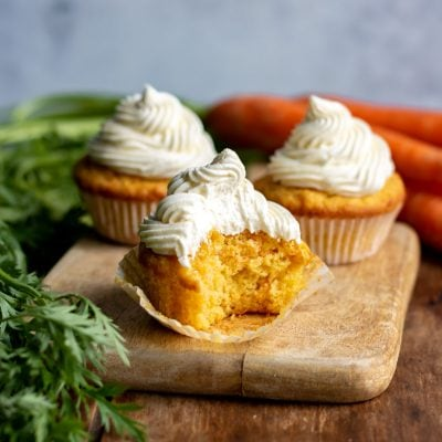 Close up of a carrot cupcake with a bite out.