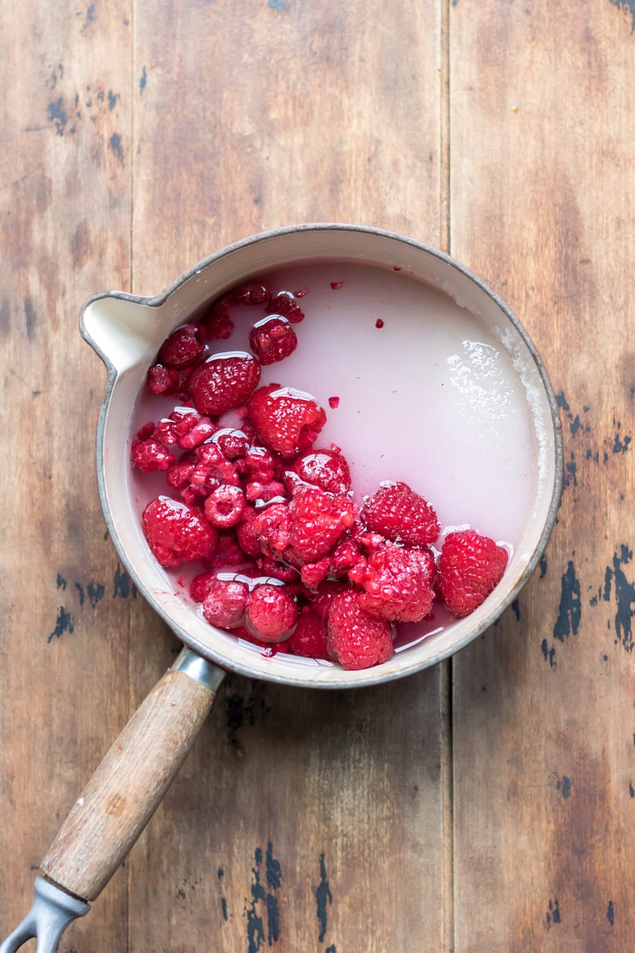 Pot with raspberries, water and sugar.