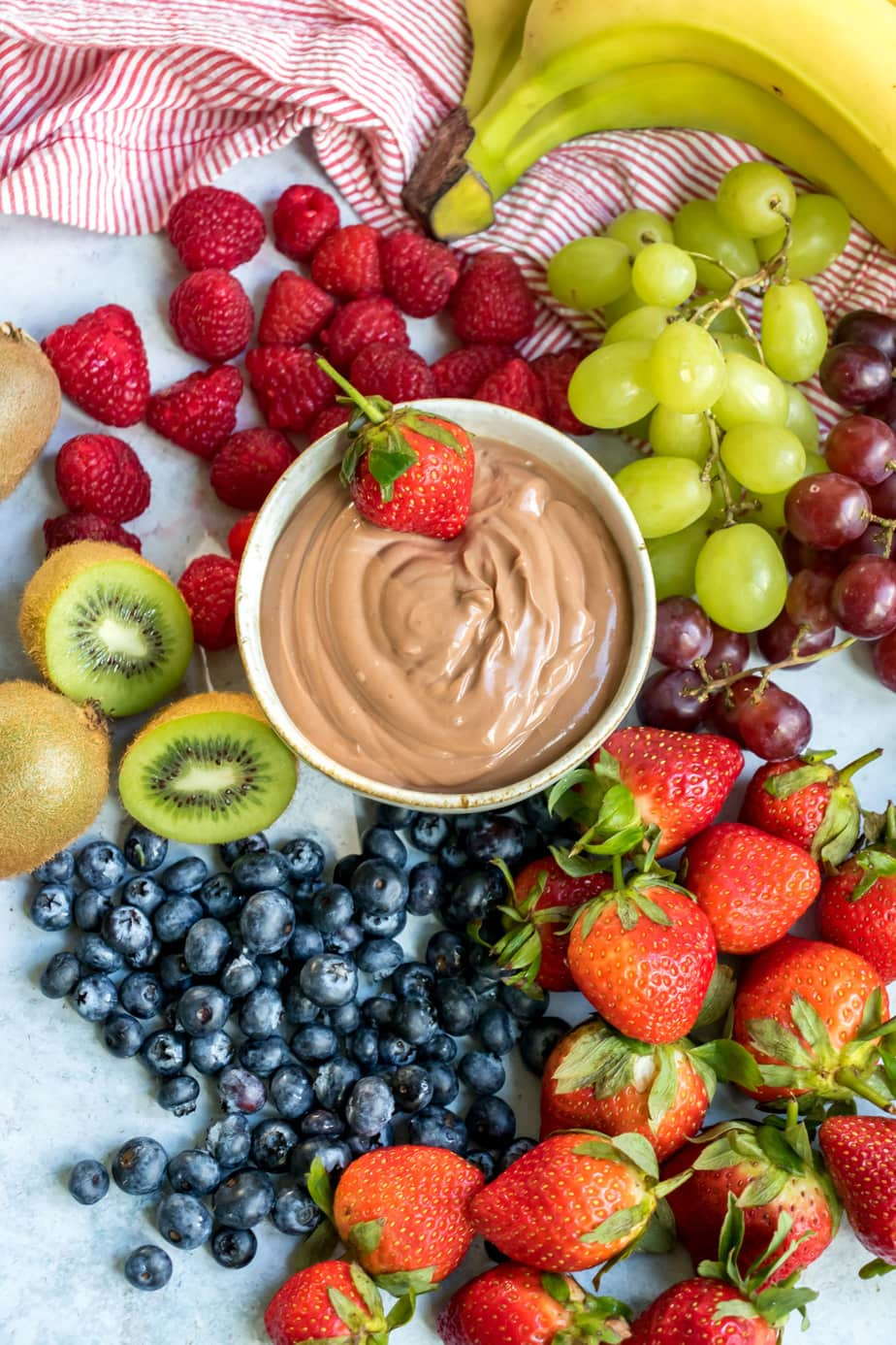 Looking down at a bowl of dip and lots of fresh fruit.