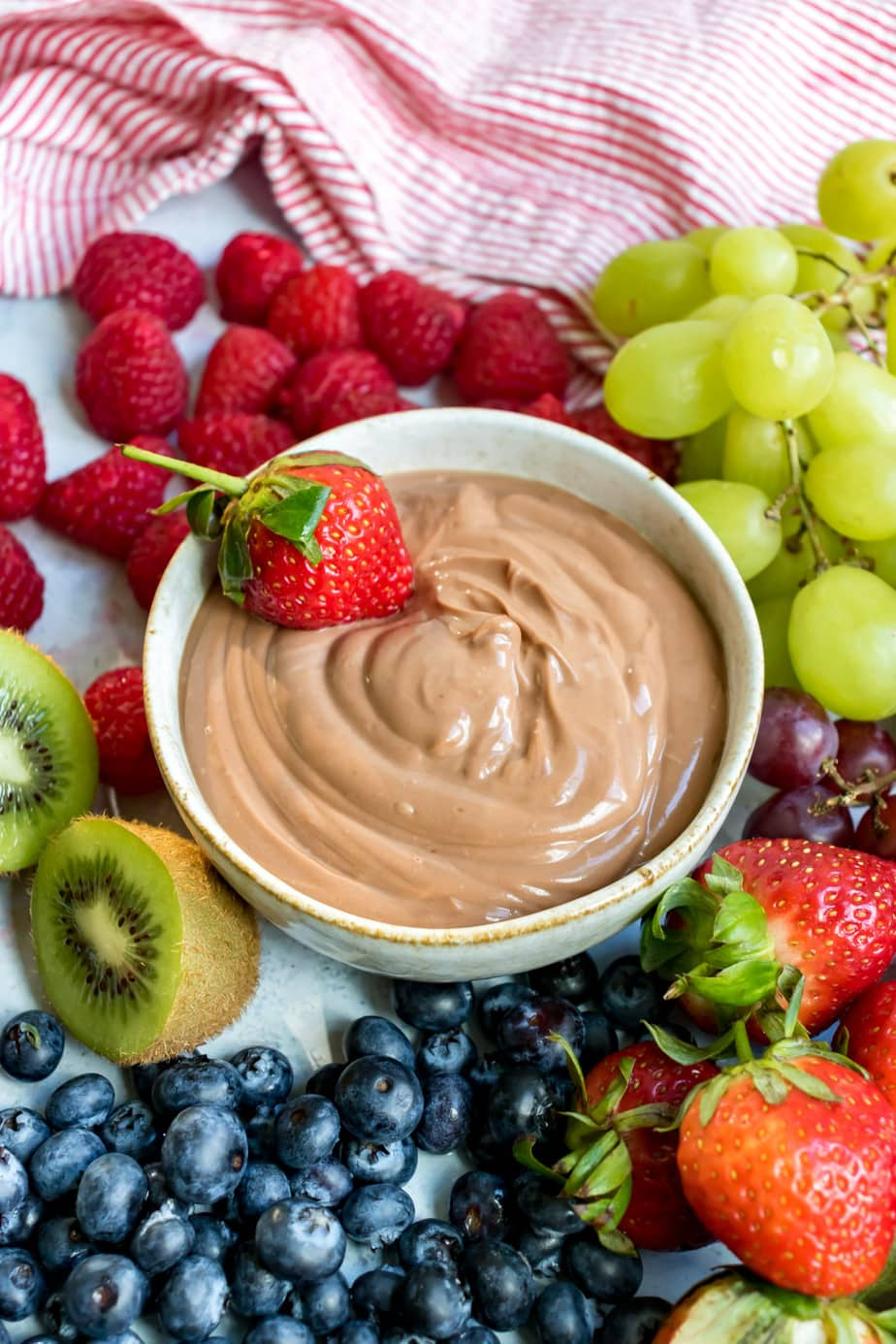 Bowl of nutella dip with a strawberry in it surrounded by fruit.