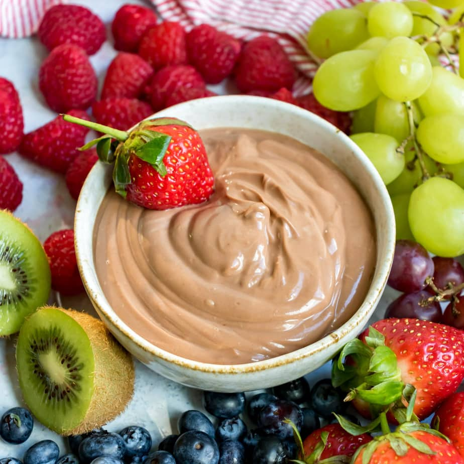 Close up of a strawberry in a bowl of nutella dipping sauce.