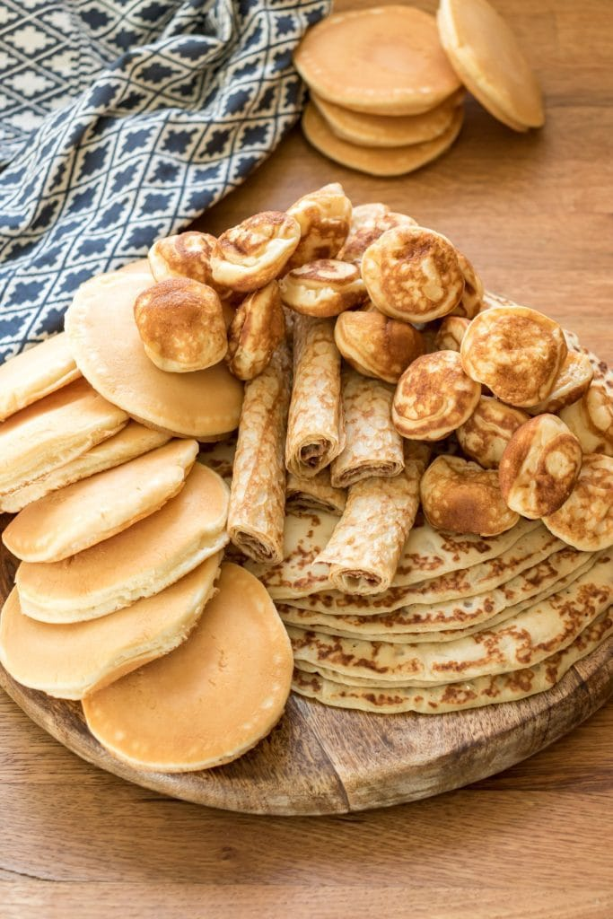 Piles of pancakes on a wooden board.