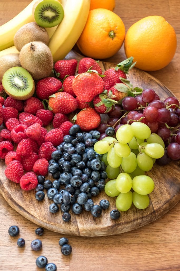 Wooden board covered in fruit.