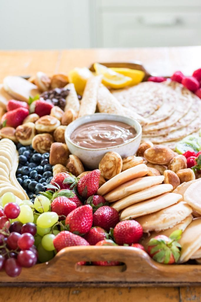Tray piled with pancakes and fruit.