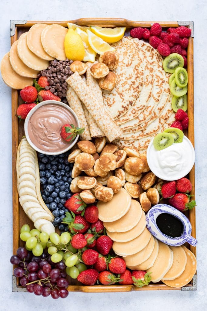 Overhead looking down on a tray full of artistically piled pancakes and fruit.