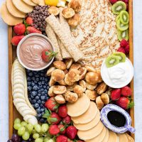 Tray full of pancakes, dip, syrup and fruit.