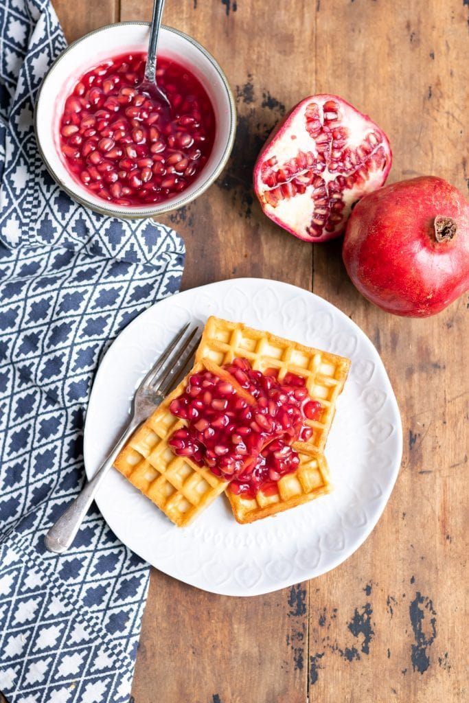 Looking down at a table with plate of waffles and compote with a bowl of pomegranate compote.