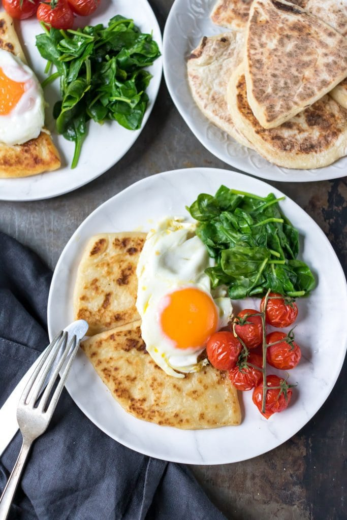 Plate with potato farls, fried egg, tomatoes and spinach.
