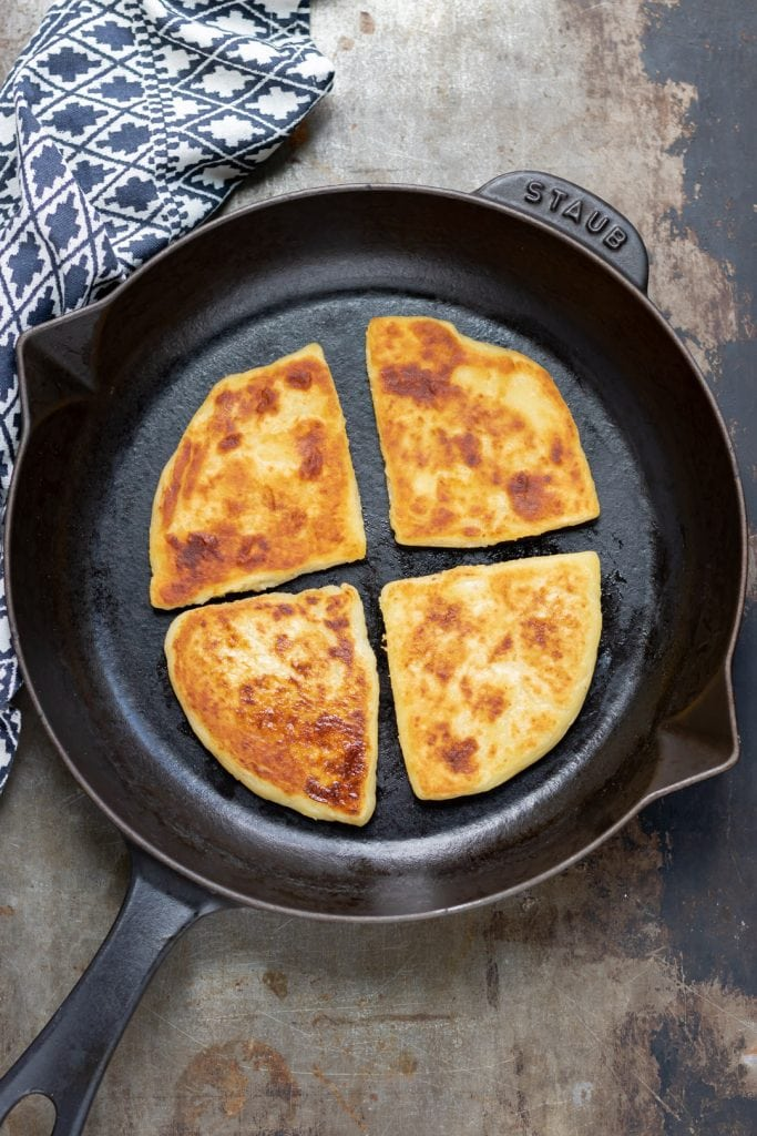Skillet with cooked potato farls.