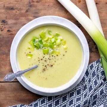 Bowl of potato leek soup next to leeks.