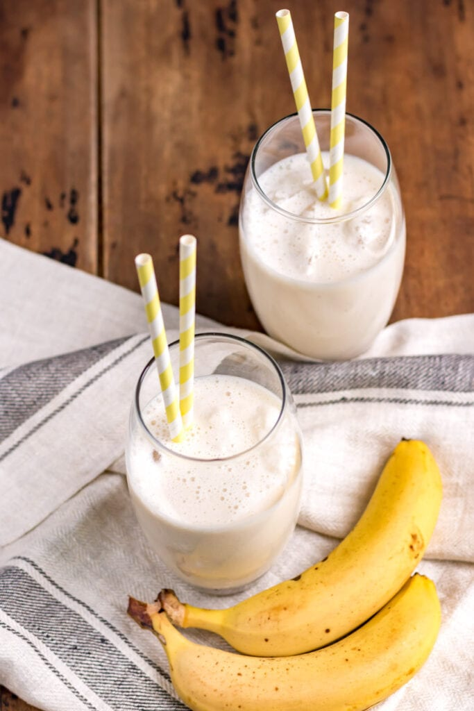 Overhead shot of two glasses of banana smoothie.