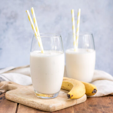 Glasses of banana lassi with straws and bananas next to them.