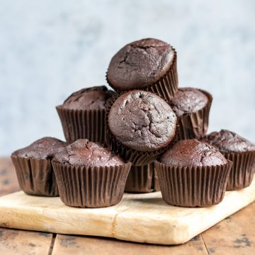 Pile of chocolate beetroot muffins on a board.