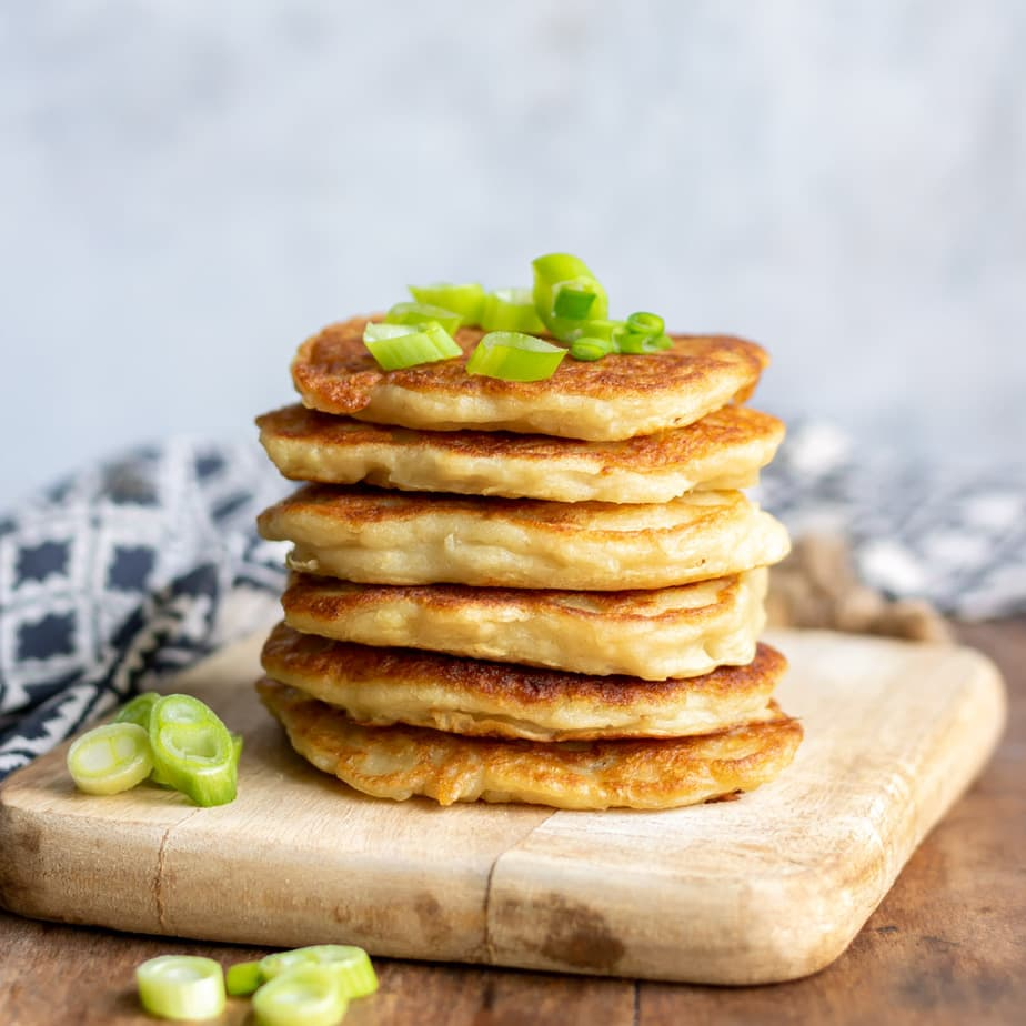 Stack of boxty with scallions on top.