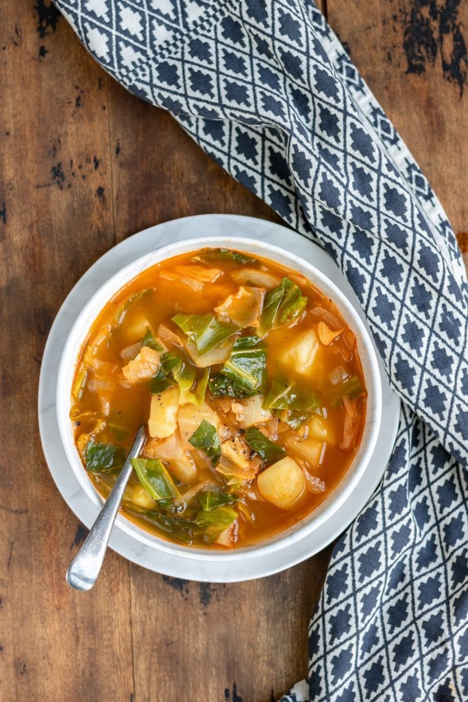 Bowl of cabbage soup on a wooden table.