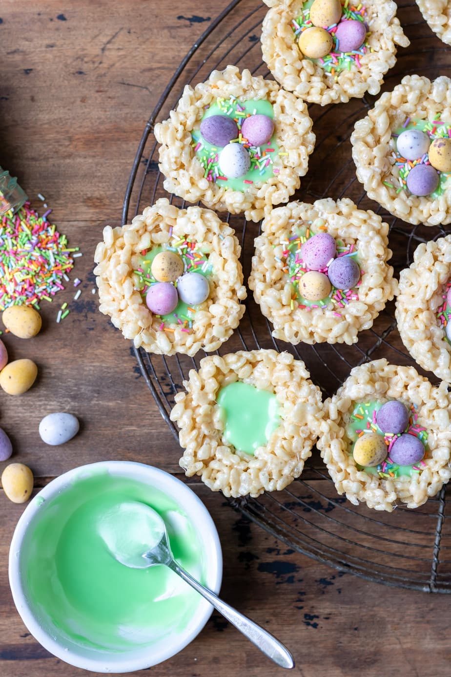 Wire rack of rice krispie nests being decorated with frosting and candy eggs.