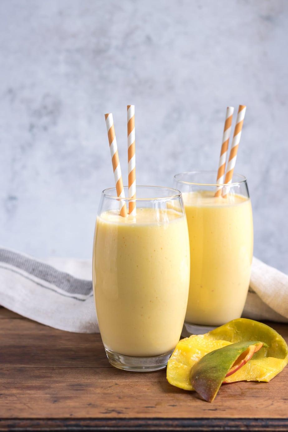 Glasses of mango shake next to mango peels.