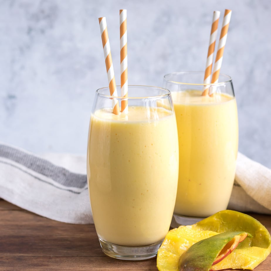 Two glasses of mango shake with striped straws.