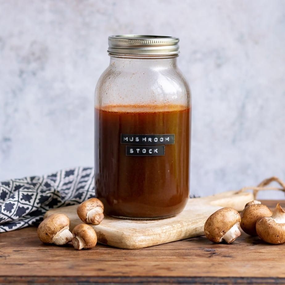 Jar of mushroom stock on a table.