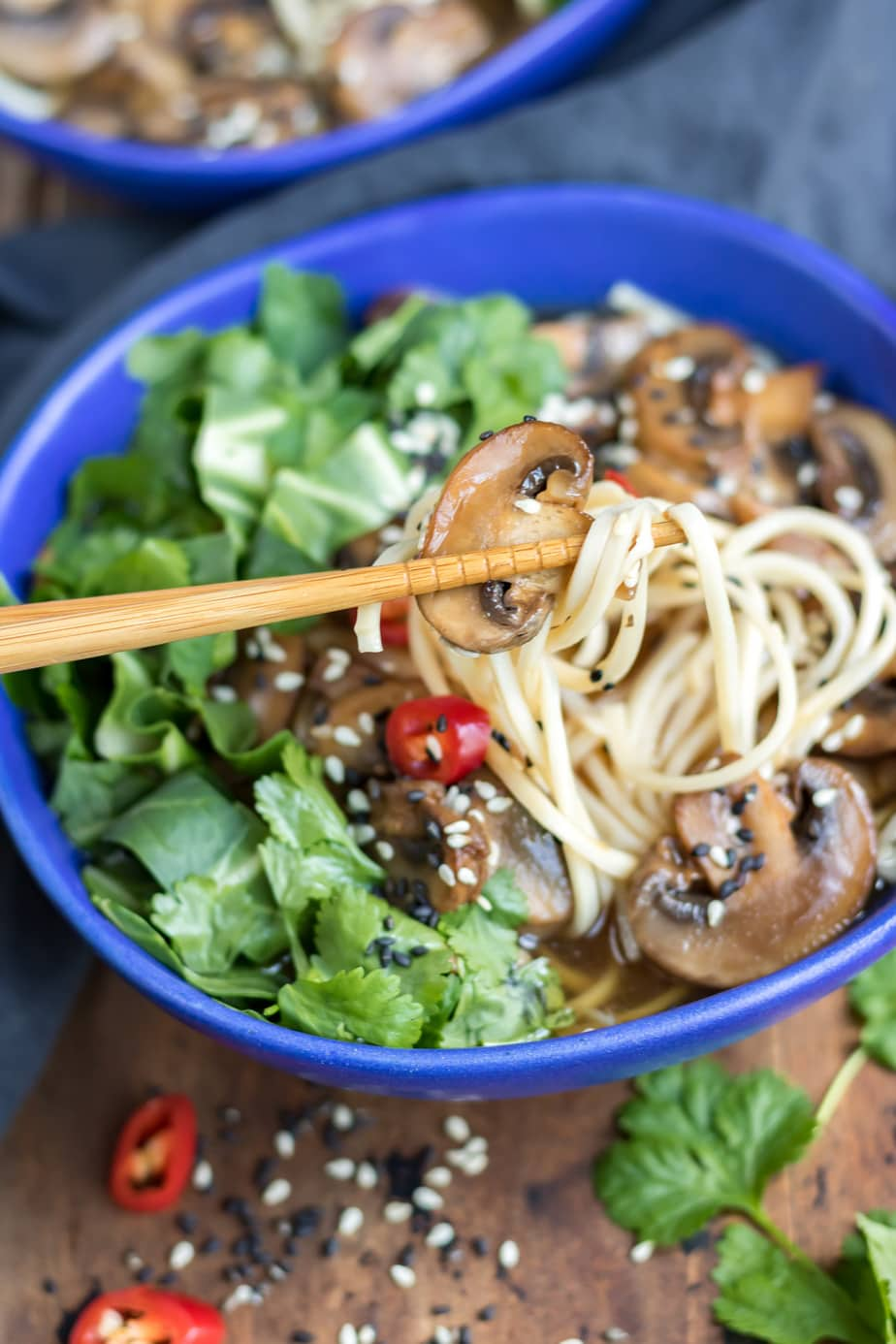 Chopsticks taking mushrooms and noodles out of a bowl.