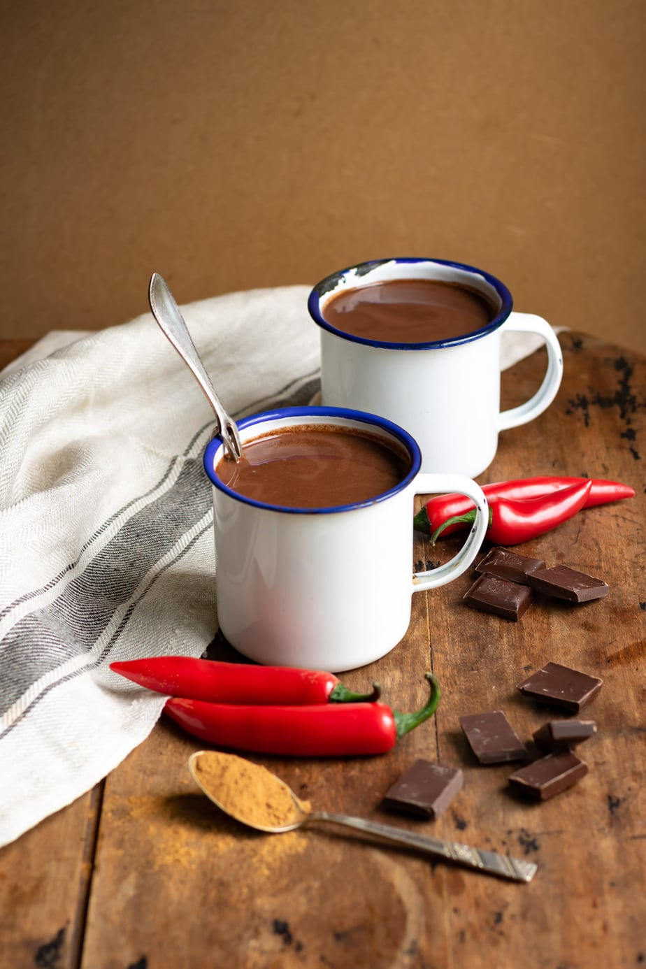 Wooden table with mugs of xocolatl, chili, cinnamon and chocolate.